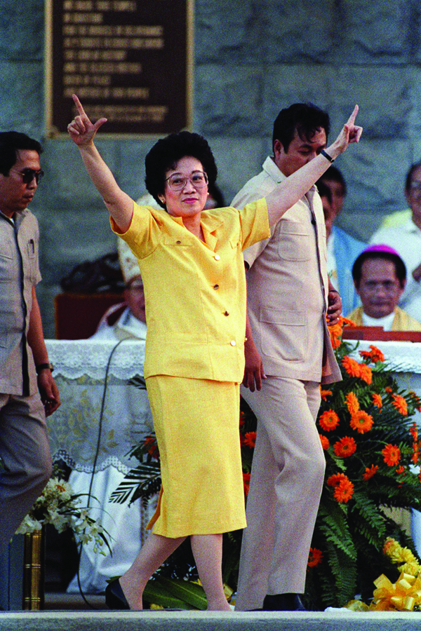 "(FILES) This file photo taken on December 8, 1989 shows Philippine President Corazon Aquino, flanked by security men, flashing her trademark ""L"" for Laban (fight) in Manila before addressing a rally of 40,000 supporters at a major highway intersection in suburban Manila, the site of the 1986 revolt that put her in power. The Philippines is prepraring to mark the first anniversary on August 1, 2010 of the death of Corazon Aquino, mother of the current Philippine president and late democracy icon whose ""People Power"" democracy movement ended decades of dictatorship. AFP PHOTO / FILES / ROMEO GACAD"