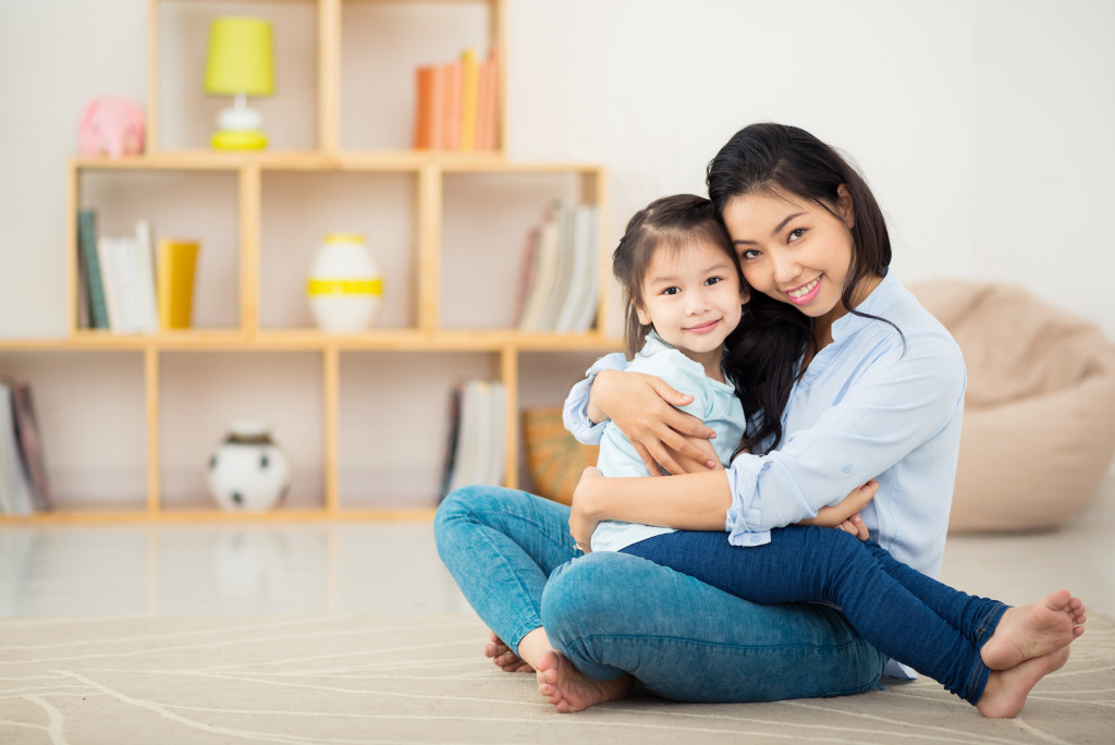 Portrait of happy young woman and her daughter hugging and looking at the camera